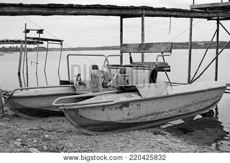 Old catamaran and wooden pier. Black and white photography