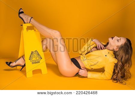 seductive woman lying in leather jacket and black panties and putting leg on wet floor sign