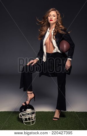 sexy woman with unbuttoned shirt putting leg on helmet and holding american football ball