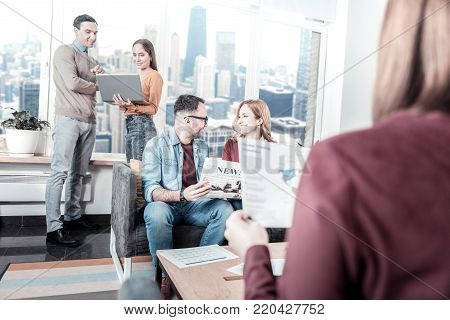 Creative encirclement. Smart busy confident workers having free time in the office communicating and having discussion.