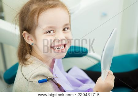 Little child looks at snowy white teeth in mirror after procedures in dentist office. Kid sits in comfortable leather chair with napkin on chest and broad smile.