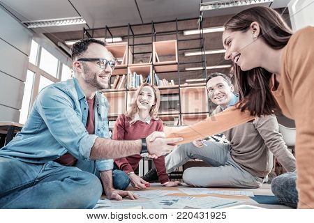 Business relationship. Young occupied satisfied employees sitting on the floor near their colleagues shaking hands and smiling.