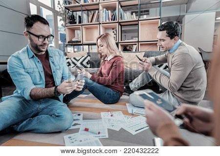 Serious and occupied. Smart concentrated busy employees sitting on the floor around papers using their smartphones and messaging.