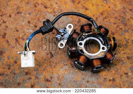 Used Motorcycle Stator on a Rusty Metal Sheet Background.