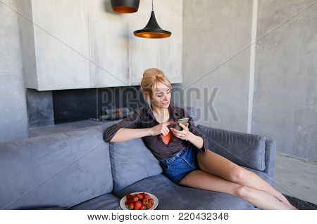 Close-up portrait of cute female portrait that relaxes after day's work and uses cellular gadget to read electronic books or women's magazines, looks ahead and tries ripe red strawberry berries, sits on gray soft couch in stylish living room with gray wal