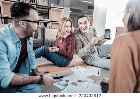 I cant believe it. Surprised handsome satisfied man sitting with colleagues smiling and showing his smartphone.