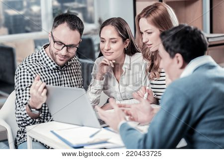 Collective creativity. Four smart occupied concentrated workers sitting together in the room using the laptop and looking at the screen.