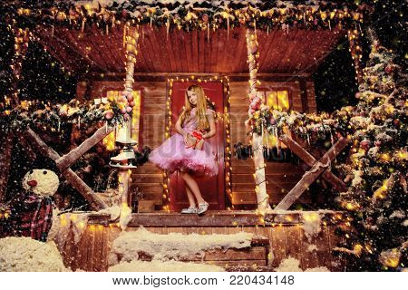 Happy child girl in a beautiful pink dress with gift in hands, stands near the house decorated for Christmas. Time for miracles. Merry Christmas and Happy New Year.