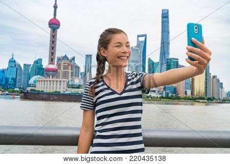China travel Asian girl tourist taking phone selfie photo on the Bund in Shanghai city vacation. Happy chinese young woman using smartphone app vlogging posting on social media. Multiracial person.