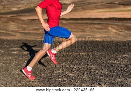 Man runner athlete running on trail run path in mountains. Legs and running shoes in motion on rocky terrain. Knee, hip, thigh, foot concept. Healthy active lower body.