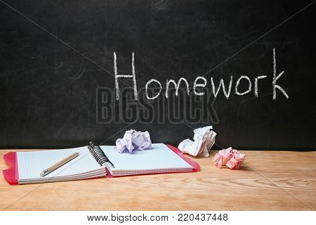 Notebook on table near chalkboard with word