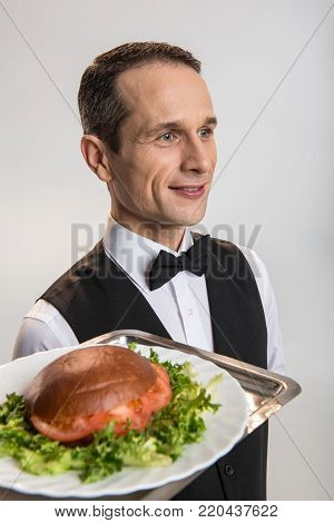 Hight class catering.  Earnest pleasant male waiter carrying salver while smiling  and posing on the isolated background