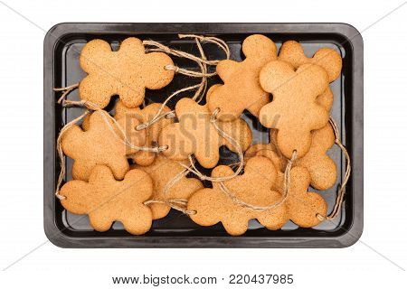 Baking sheet with gingerbread men isolated on white background closeup