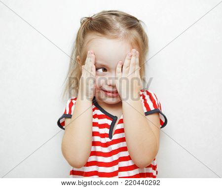 Funny little girl in striped T-shirt that cheats in hide and seek game. Child covers half of face with palm and spys with other eye during childish game portrait photo.
