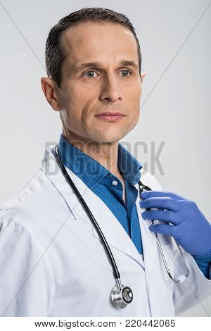 Responsible job.  Earnest attractive male doctor tipping stethoscope while reflecting and treating people