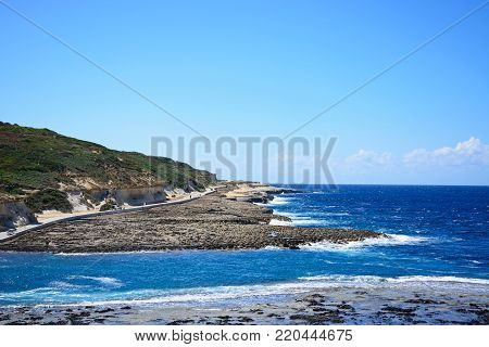 MARSALFORN, GOZO, MALTA - APRIL 3, 2017 - View along the coastline with rocks in shallow water in the foreground, Redoubt, Marsalforn, Gozo, Malta, Europe, April 3, 2017.