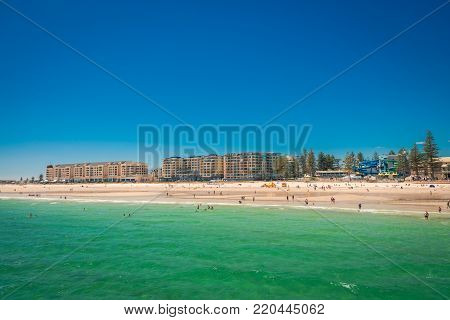 Glenelg, South Australia - February 28, 2016: People with surf life saving patrol at Glenelg beach viewed from jetty on a bright summer day