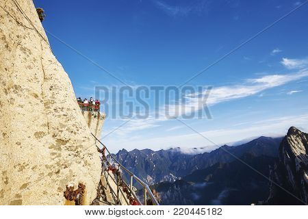 Mount Hua, Shaanxi Province, China - October 6, 2017: Tourists on a view point above the Plank Road in the Sky, worlds most dangerous hike.