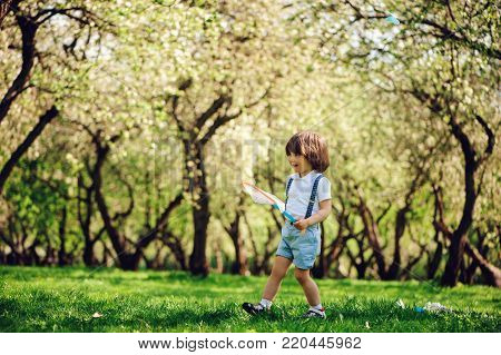 cute toddler child boy with long hair in stylish outfit playing with toy car on the walk in summer or sping garden, sitting on big tree