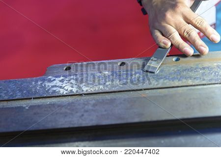 The hand of workers scraping the slide way of CNC machine.The flatness process for CNC machine part