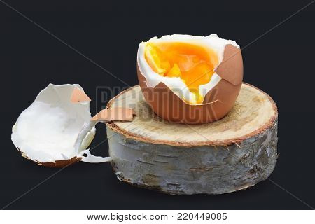 Boiled fresh egg for the breakfast on the wooden birch stand for eggs isolated on dark blue. Broken beige hen egg and pieces of shells, bright orange yolk