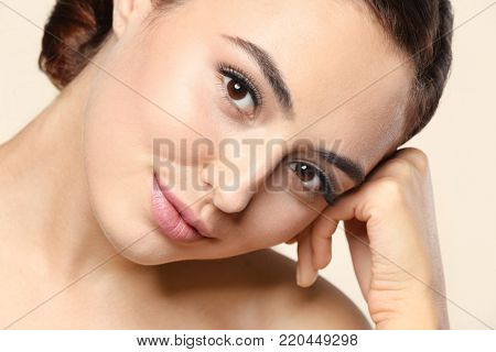 Beautiful young woman with eyelash extensions on color background, closeup