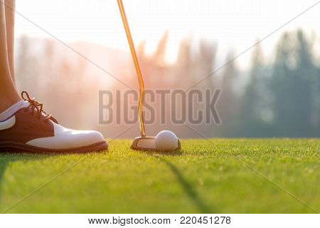Golfer asian woman putting golf ball on the green golf on sun set evening time.  Healthy and Lifestyle Concept.