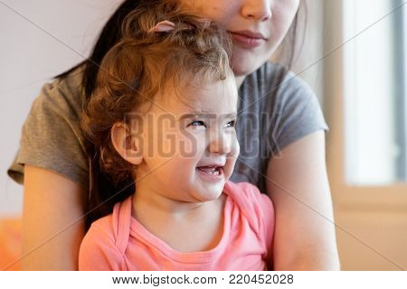 child laughs sitting at the mother's lap.