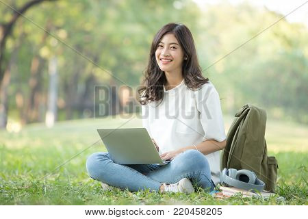 Asian Woman Holding Smartphone With Attractive Smiling At Garden. People Lifestyle Concept.