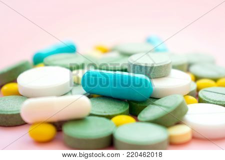 Opioid Pills. Opioid epidemic and drug abuse concept. Different tablets, pills, capsule on a pink background.  Heap mix therapy drugs. Selective focus