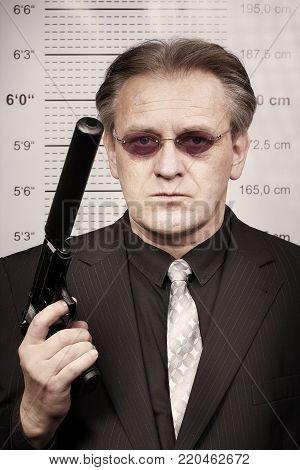 Older criminal man portraited with silenced pistol in front of mug board