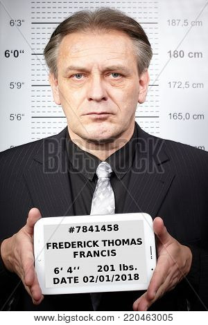 Older man portraited on police station in front of mug board with fake personal data on tablet