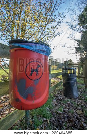 Red dog waste bin. Responsible pet ownership. Cleaning up dog mess. Bin outside UK park.