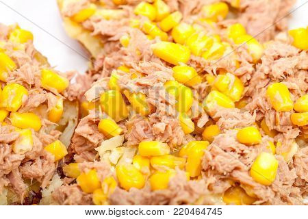 Close up of tuna and sweetcorn on baked potato. Tinned tuna fish mixed with with tender yellow corn off the cob as a nutritional filling.