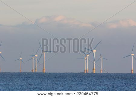 Offshore wind farm. Clean alternative energy turbines on the sea horizon. Beautiful ethereal scenic image representing sustainable renewable resources.