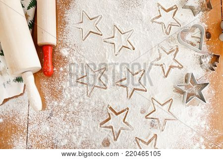 Heart and star shaped cookie cutters made by professional unknown cook, rolling pins for making thin dough. Home made Christmas cookies ready to be baked. Gingerbread made of different forms