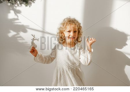 Playful cheerful little beautiful girl with blonde curly hair plays with toy deer, dressed in festive white dress, ready to recieve Christmas presents, isolated over white background with shadow