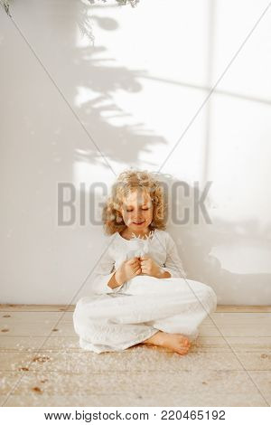 Restful adorable small kid dressed in long white dress, plays with Christmas toy deer, sits crossed legs on wooden floor, isolated over white studio background. Happy child plays with favourite toy