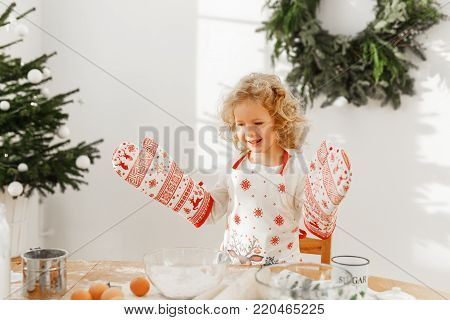 Hard working little child cook wears big kitchen gloves, prepares delicious pastry instead of mother, confident in success, helps parents about house, stands at spacious room decorated with fir tree