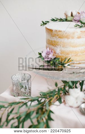 Beautiful wedding round cake with floral decorations on glass cake stand.