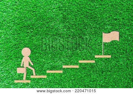 Walking Business man carry a bag up the stairs walks up to the goal to succeed paper cut of a green background