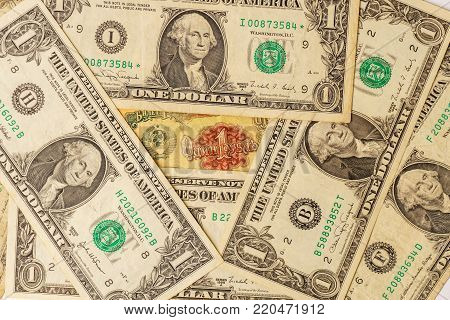 Old banknote of the former Soviet Union with american one dollar bills. 1 ruble USSR and many one dollar bills USA.