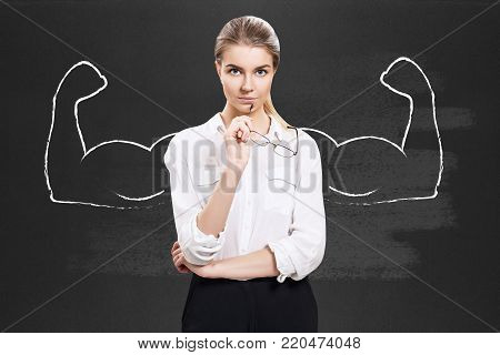 Business woman stands over chalkboard with drawn powerful hands.