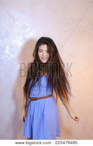 Cute young woman smiles beautifully and in high spirits looks and poses, changing poses to camera in bright silvery confetti, standing against background of light wall in room. Dark-haired woman dressed in blue dress. Concept of beautiful and happy girl