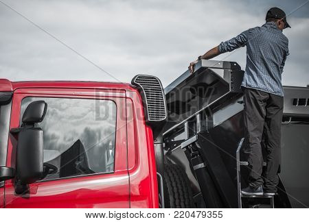 Truck Driver Checking the Load in His Dump Truck. Heavy Duty Transportation Theme.