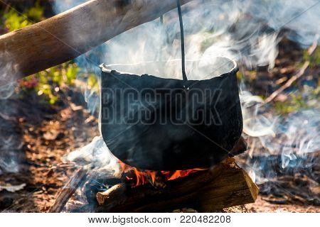 cauldron in steam and smoke on open fire. outdoor cooking concept. old fashioned way to make food