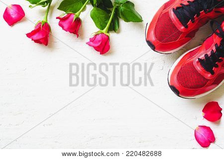 Red sport shoes  and red roses on white wooden background, Valentines sports background and greeting card for any anniversary holiday background concept top view with copy space.