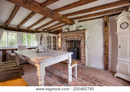 Tastefully modernised dining room withing 16th Century English cottage with traditionally styled decor sympathetic to the original period with dining table and bench stool, cast iron stove, upright clock, exposed timber and beams, brick floor and leaded w