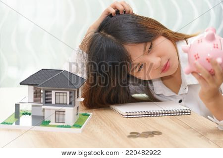 Stressed woman with running out of money in piggy bank and her house - dept and installment payment concept