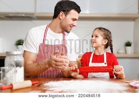 Children, baking, family concept. Cheerful brunet male wears apron and kneads dough, happy girl holds rolling pin, ready to help her father, sit together at kitchen, prepare dough for cookies